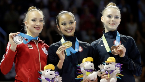 The United States' Laura Zeng, center, stands with Canada's Patricia Bezzoubenko, left, and the United States' Jasmine Kerber after winning the gold medal during rhythmic gymnastics clubs competition