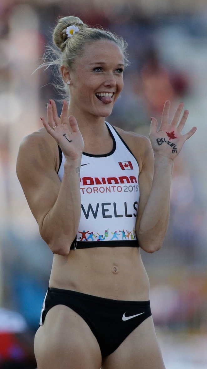 Sarah Wells, of Canada, waves to a camera before running in the finals