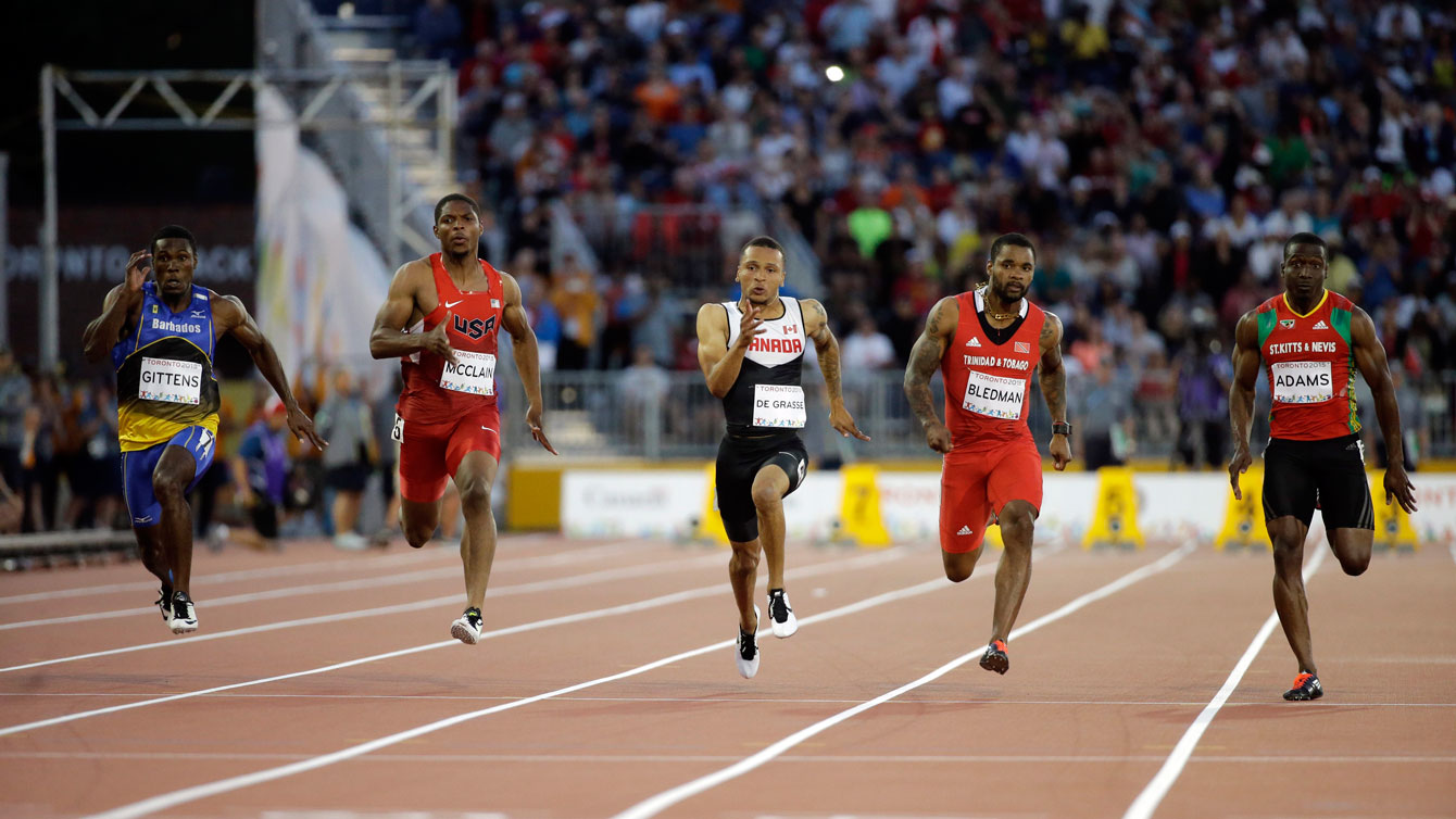 Andre De Grasse (centre) speeds away to 100m Pan Am Games victory on July 22, 2015 in Toronto.