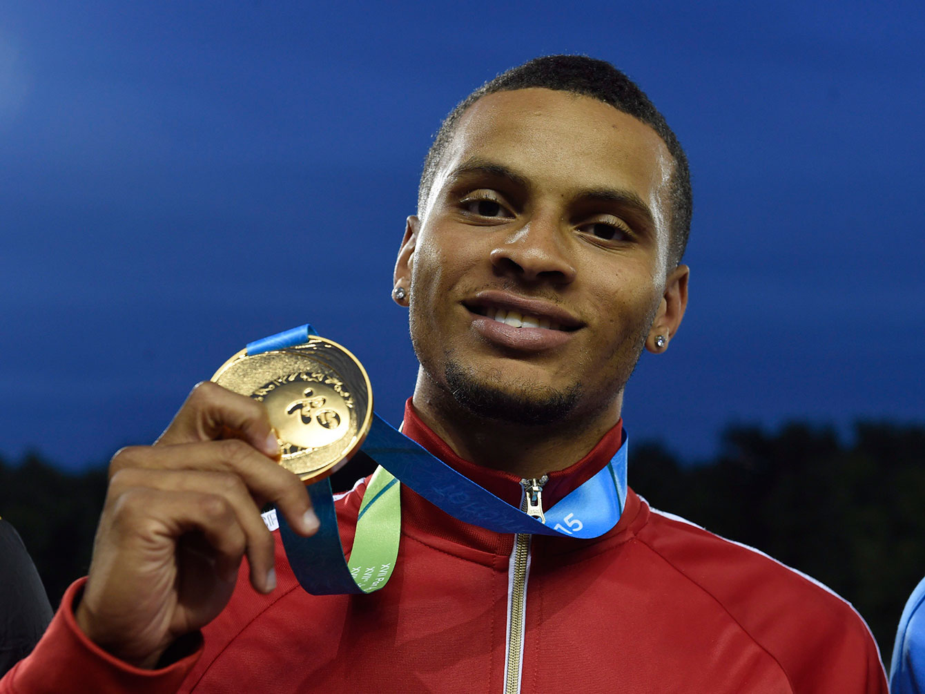 Andre De Grasse holds up his 200m Pan Am Games gold medal on July 24, 2015 in Toronto.