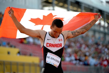 Andre De Grasse holding the Canadian flag
