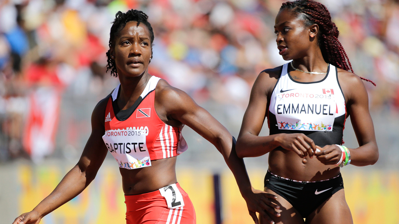 Kelly Ann Baptiste (left) looks at the scoreboard after heats, next to Canada's Crystal Emmanuel, who also advanced to the Pan Am Games 100m semifinals on July 21, 2015.
