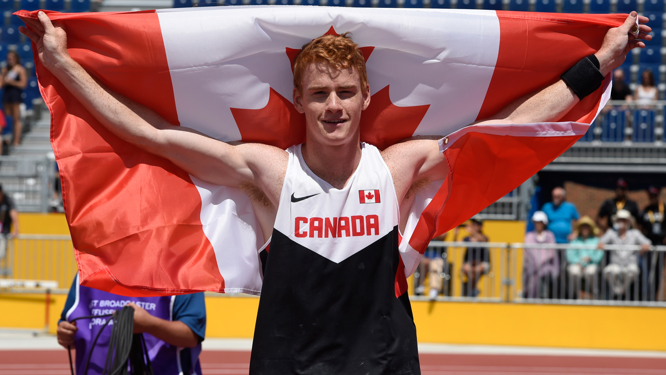 Shawn Barber celebrates with the Canadian flag after winning Pan Am Games pole vault competition on July 21, 2015.