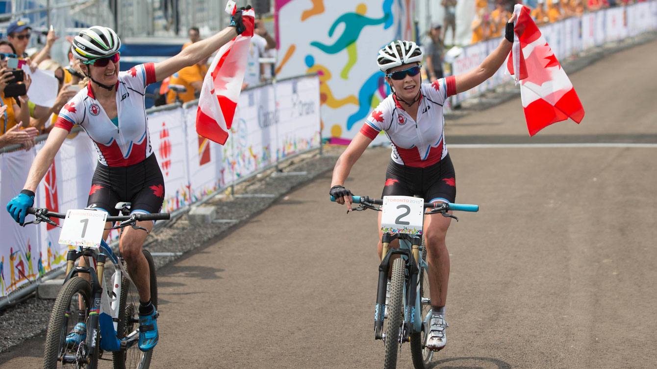 Emily Batty (right) and Catharine Pendrel raise the flag after finishing 1-2 at Pan Am mountain bike on July 12, 2015.