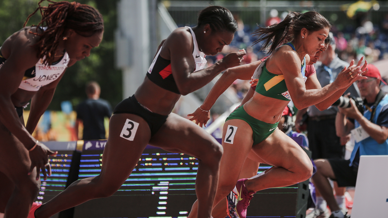 Khamica Bingham (centre) takes off at the start of the women's 100m Pan Am Games heats in Toronto on July 21, 2015.
