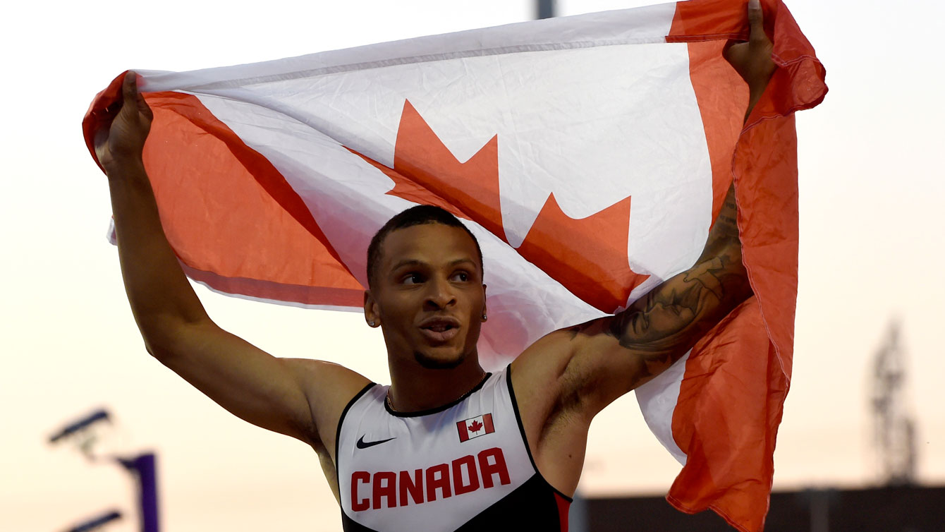 Andre De Grasse with the Canadian flag after winning the Pan Am Games 100m on July 22, 2015 in Toronto.