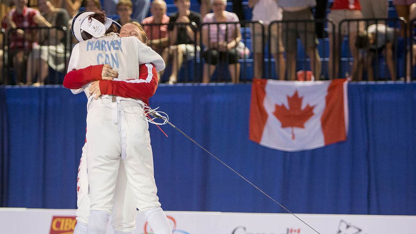 Teammates Kelleigh Ryan (red jacket) and Eleanor Harvey celebrate winning against the United States in the Team Women's Foil gold medal fencing match at the Pan American Games on July 25, 2015.