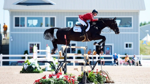 Tiffany Foster on her horse jumping over a hurdle