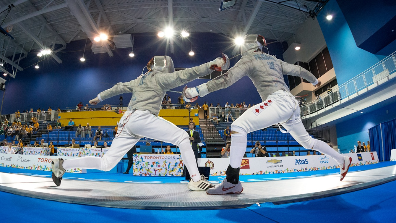 Joseph Polossifakis (Canada) fences against Stryker Weller of the Virgin Islands in the initial elimination rounds of Men's Sabre Competition at the Pan-American Games in Toronto, Canada.
