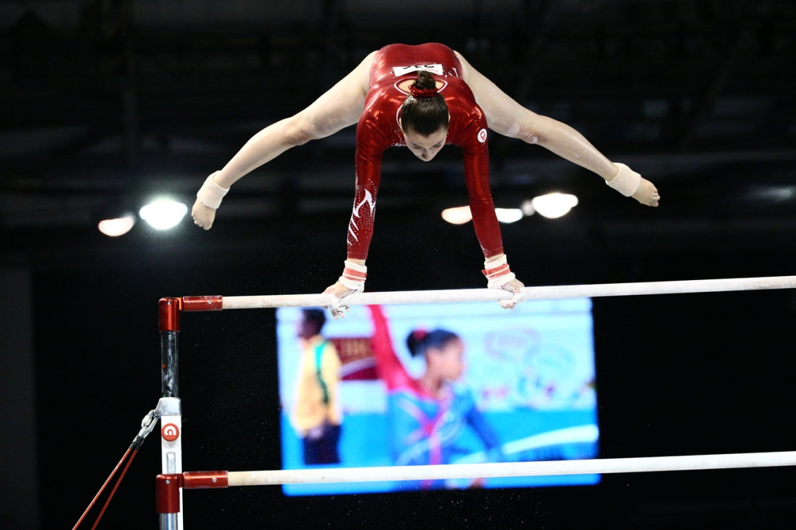 Victoria Woo competes on the uneven bars. (Photo: John Fernandez)