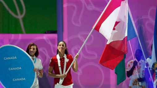 Kia Nurse proudly carries the flag during the TO2015 Closing Ceremony.