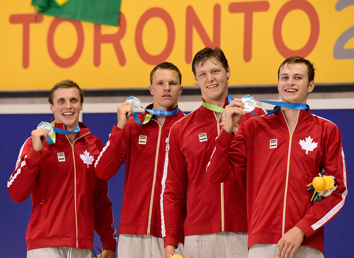 Canadian swimmers Santo Condorelli, left to right, Karl Krug, Evan Van Moerkerke and Yuri Kisil smile as they hold their medals after a second place finish in the men's 4x100 freestyle at TO2015.