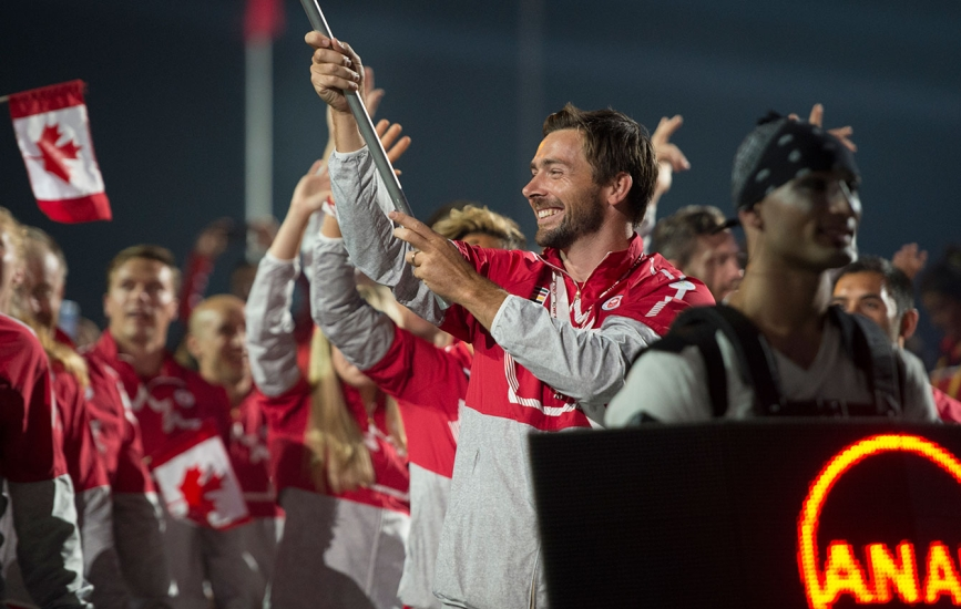 Mark Oldershaw carries the flag in for Canada at the Opening Ceremony for TO2015. The team in its Hudson's Bay kit.