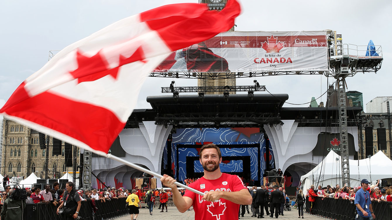 Mark Oldershaw waves the flag prior to Canada Day celebrations on Parliament Hill on July 1, 2015 (Greg Kolz for Canadian Olympic Team).