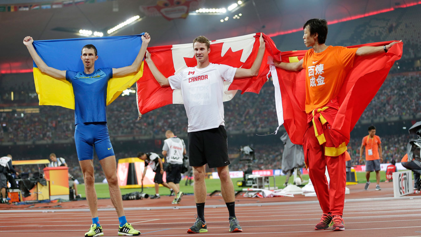 Derek Drouin (centre), stands with Bohdan Bondarenko (left), and Guowei Zhang at the conclusion of the high jump at the world championships in athletics on August 30, 2015 in Beijing, China.