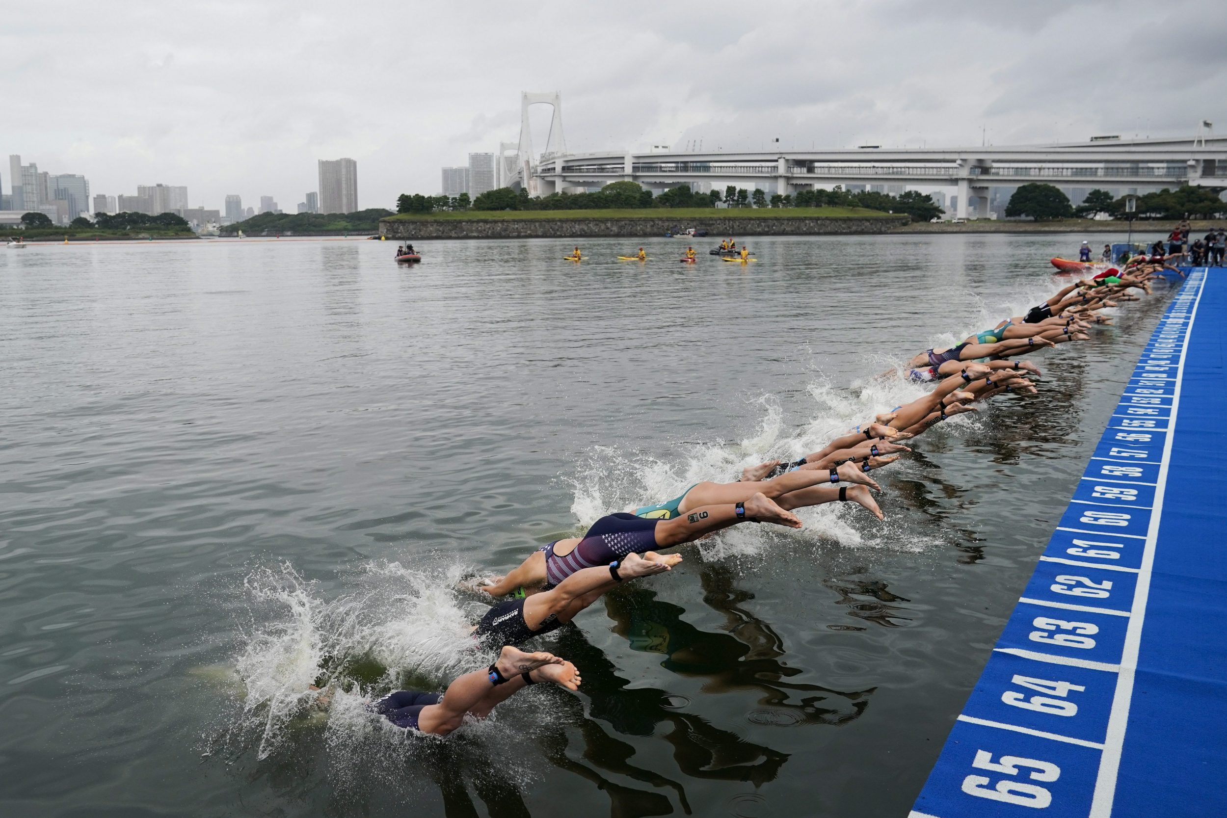 Women dive into water at Triathlon test event at the Odaiba Marine Park