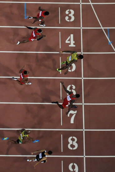 Andre De Grasse (lane nine) leans in for bronze as Usain Bolt (5) and Justin Gatlin (7) battle for gold and silver in the closing moments of the 100m final at the IAAF World Championships in Athletics in Beijing, China on August 23, 2015.