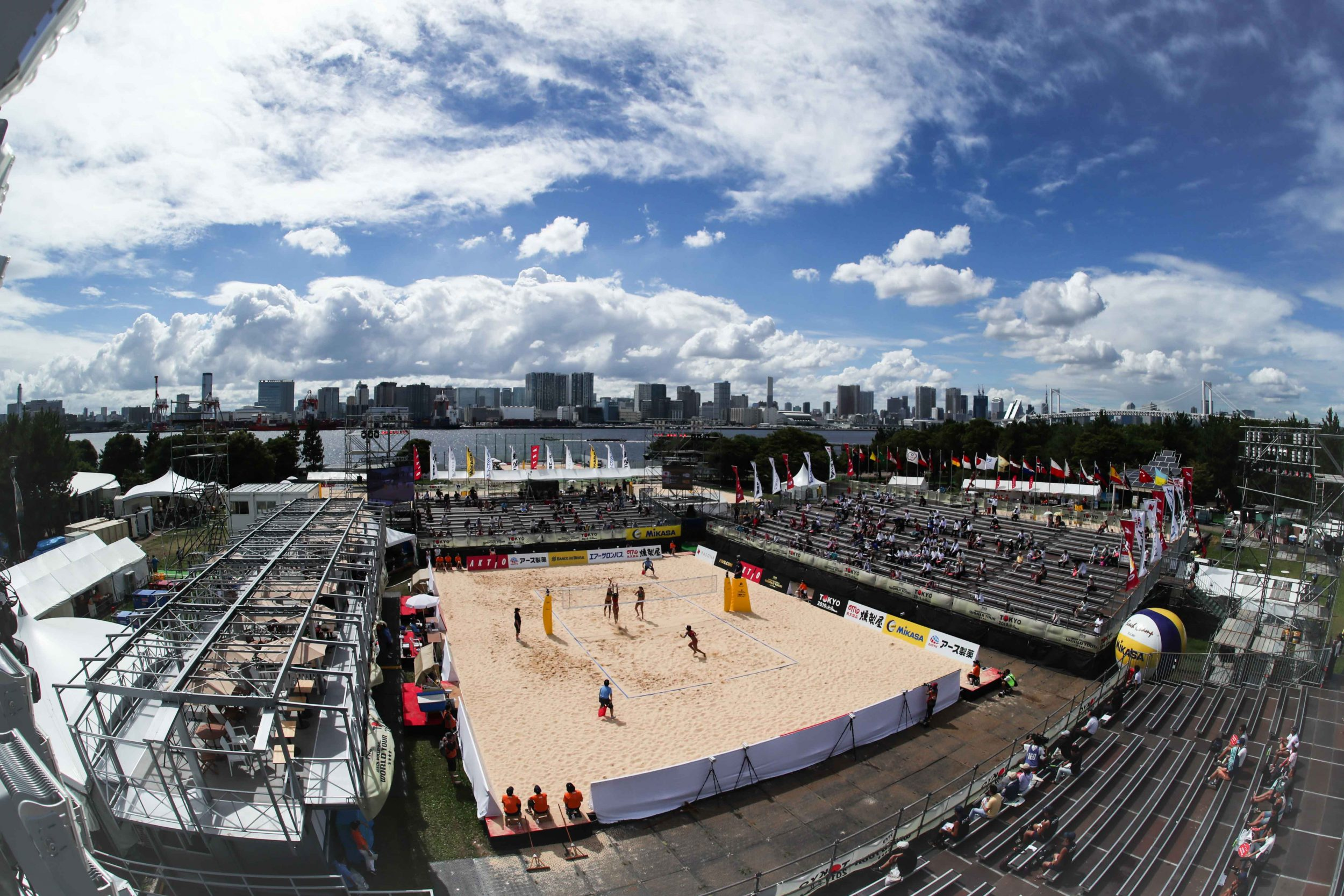 Players play beach volleyball at test event at Shiokaze Park