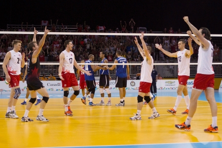 Members of the Canadian men's volleyball team celebrate the match-winning point