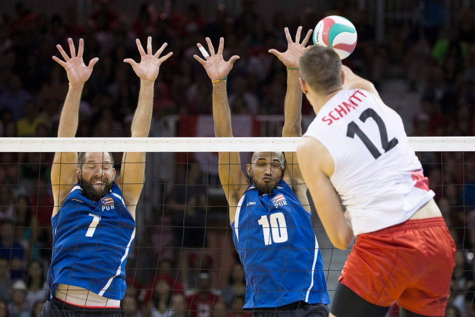 Puerto Rico's Enrique Escalante (left) and Ezequiel Cruz (centre) jump totry and block a spike from Canada's Gavin Schmitt