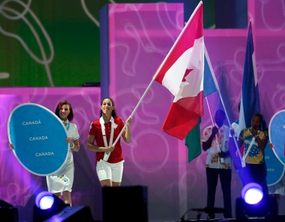Basketball player Kia Nurse carries in the Canadian flag during the parade of nations at the closing ceremony