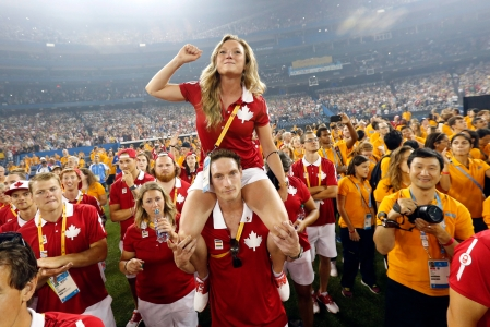 Canadian athletes Rosannagh MacLennan sits on the shoulders of Joshua Binstock as they listen to the entertainment