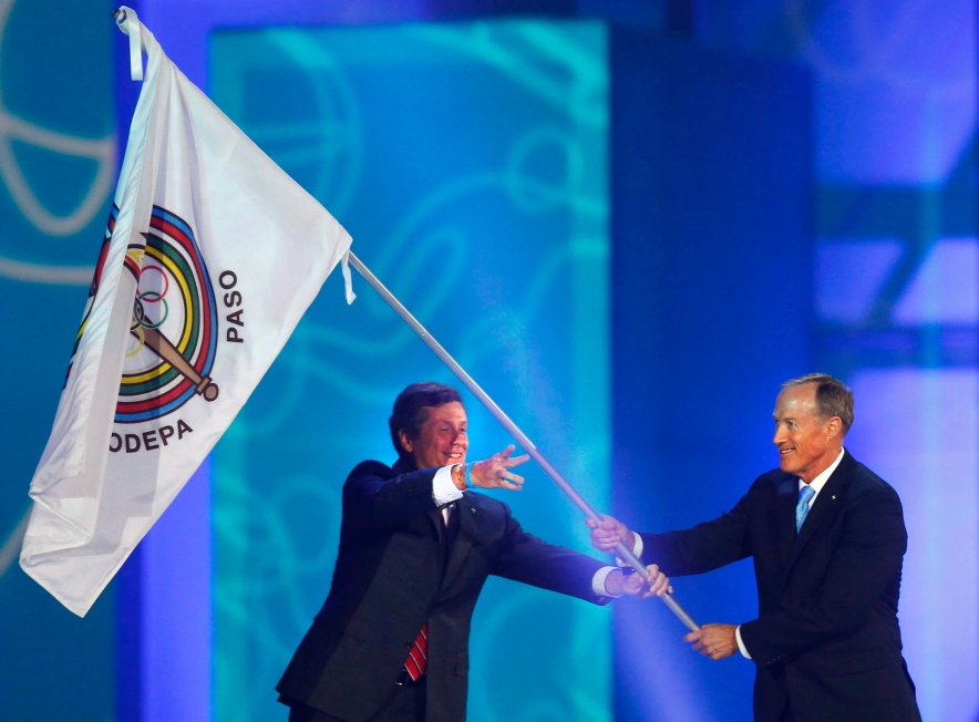 Toronto Mayor John Tory, left, passes the Pan American Sports Organization flag