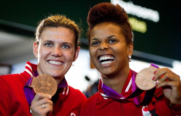Female soccer players posing with medals