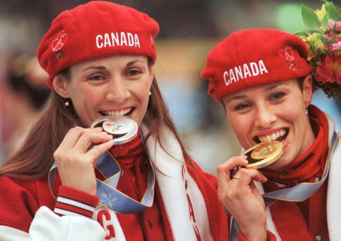 Susan Auch and Catriona Le May Doan bite their medals