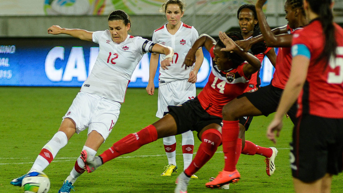 Christine Sinclair (left, in white) sets up to shoot against Trinidad and Tobago on December 13, 2015 at the invitational tournament in Natal. Sinclair scored at the 85th minute to tie Mia Hamm with 158 career goals for second in the all-time list (Photo: Vlademir Alexandre/Allsports).