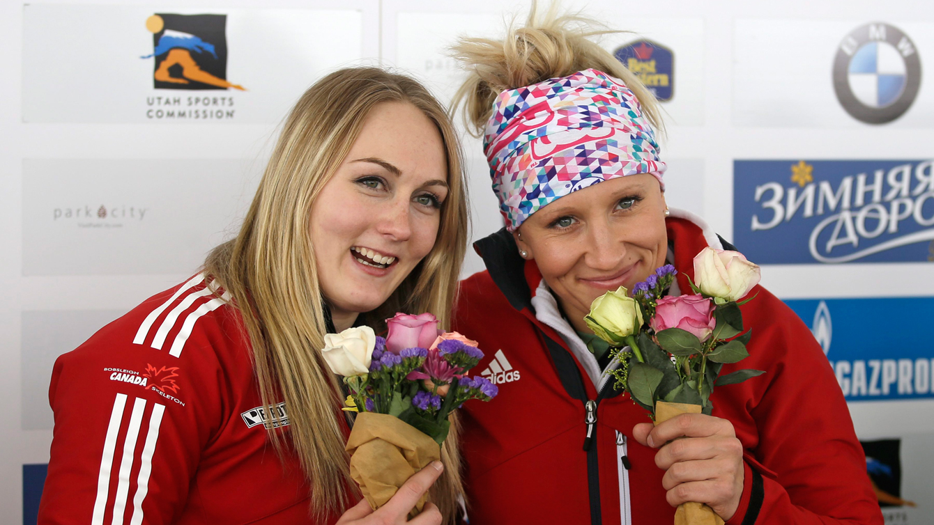 Kaillie Humphries, right, and Melissa Lotholz pose with their flowers during a ceremony after winning the women's bobsled World Cup race Friday, Jan. 15, 2016, in Park City, Utah. (AP Photo/Rick Bowmer)