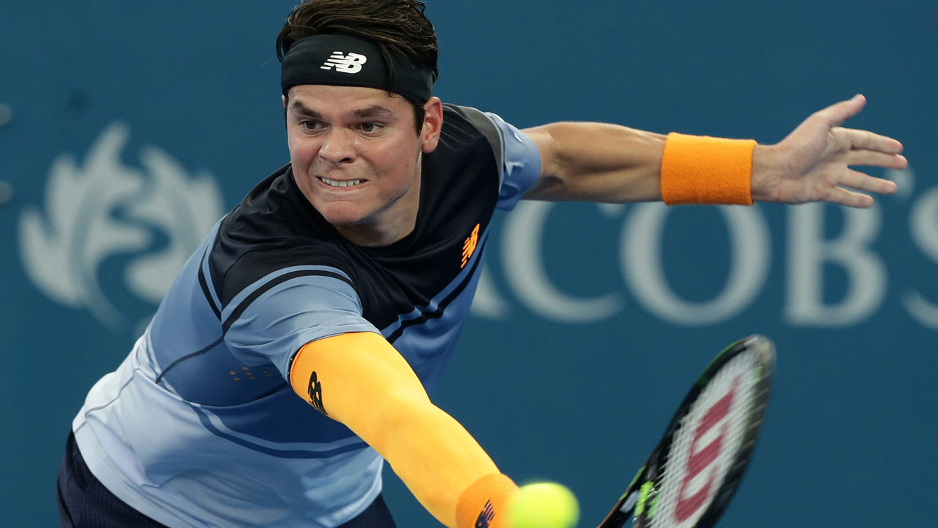 Milos Raonic reaches for a return against Bernard Tomic in the Brisbane International semifinals on January 9, 2016.
