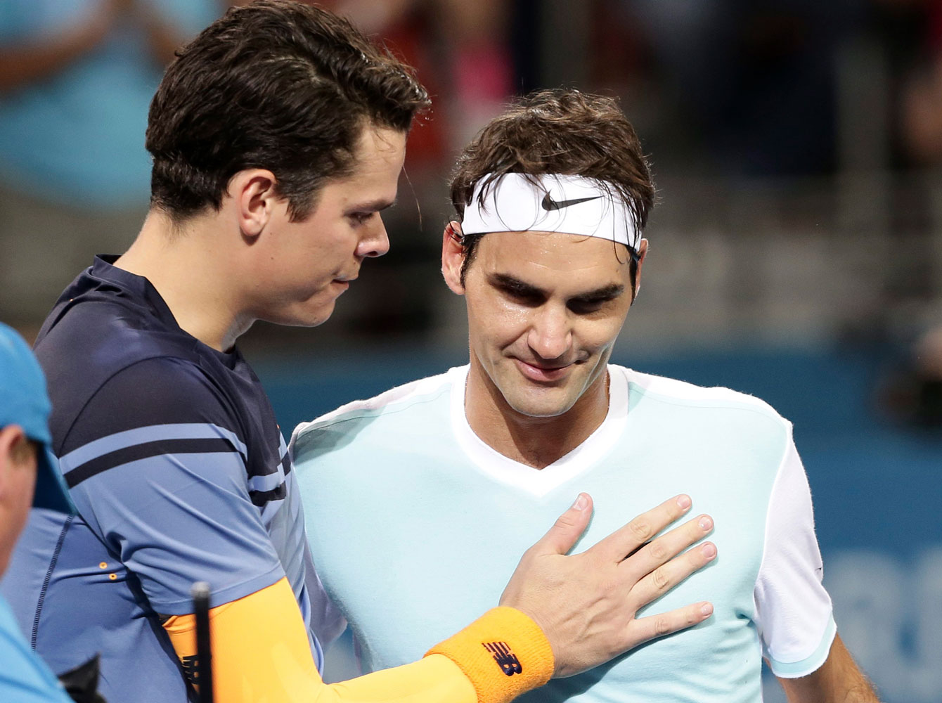 Milos Raonic consoles Roger Federer following the Brisbane International final where the Canadian prevailed on January 10, 2016.