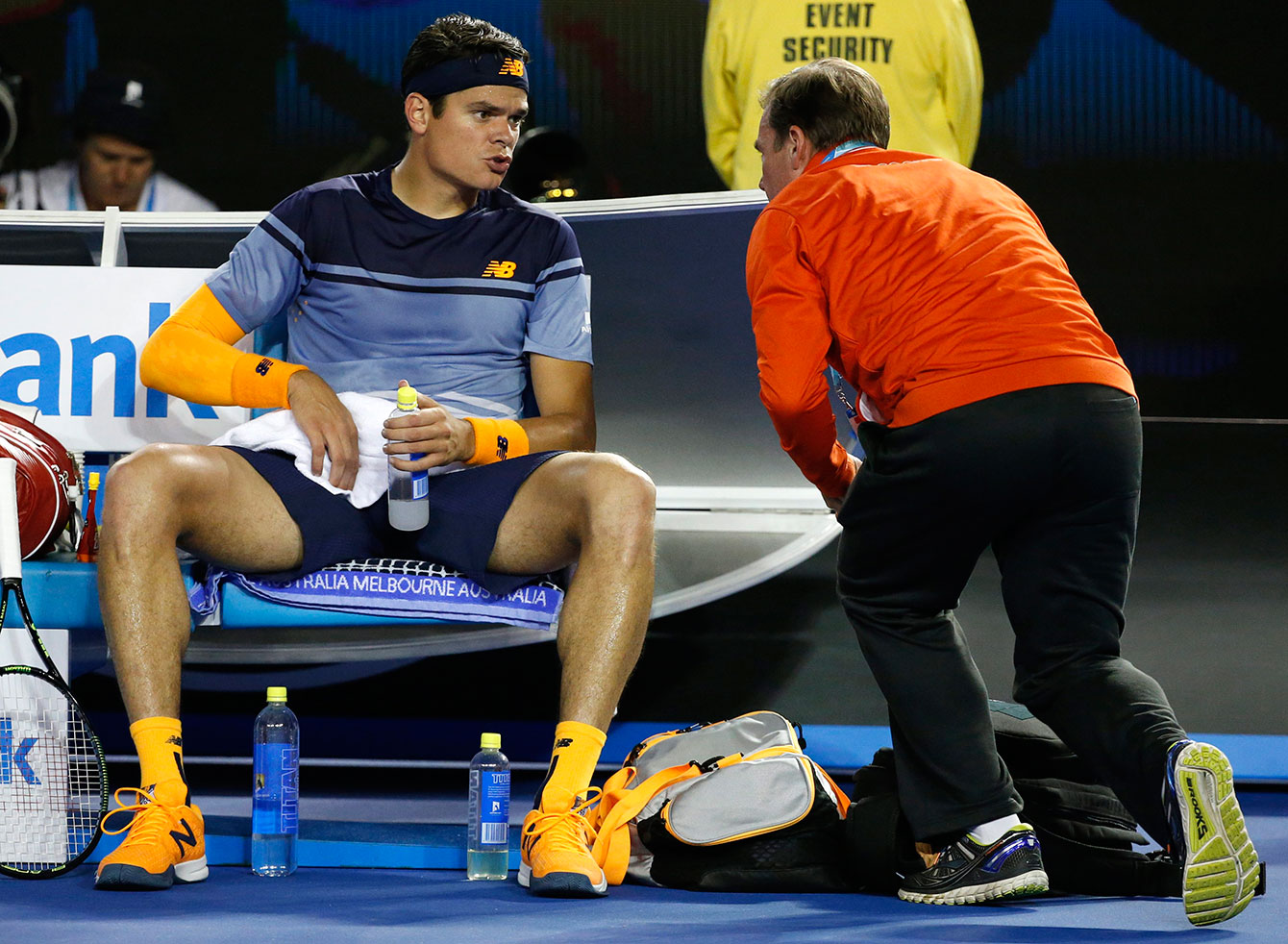 Milos Raonic speaks to a trainer during the fourth set at the Australian Open semifinals on January 29, 2016.