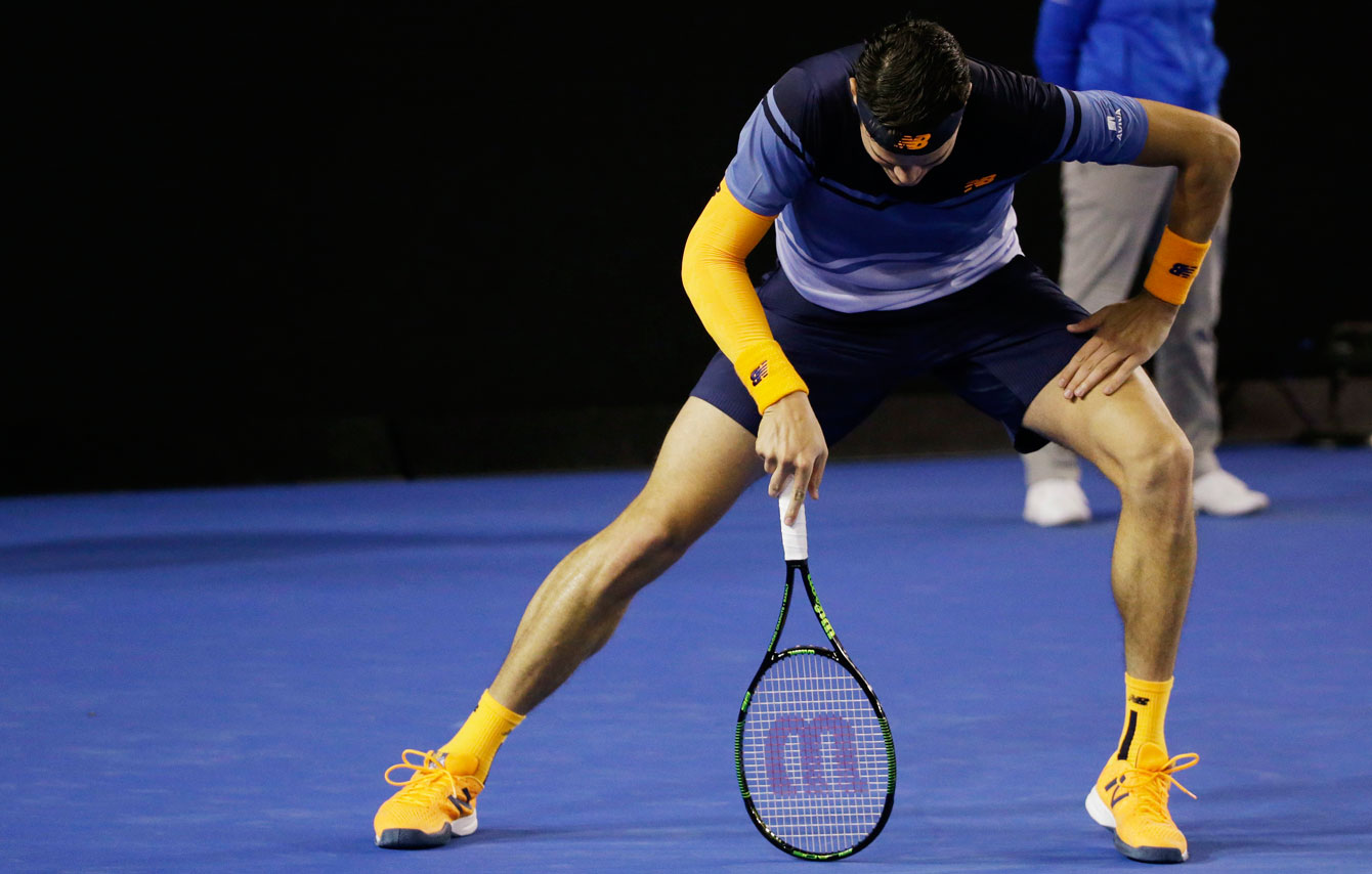 Milos Raonic uses his racket to stretch out an injured right leg during his Australian Open semifinal tie on January 29, 2016.