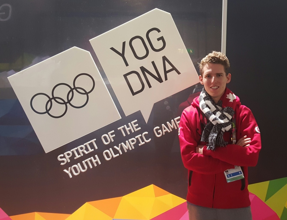 Eric posing in front of a YOG background