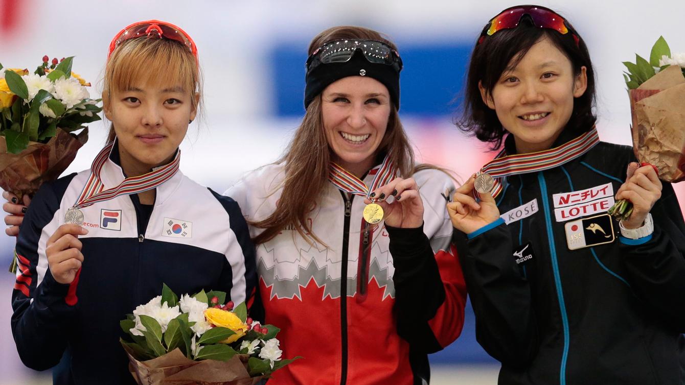 Ivanie Blondin (centre) holds up her mass start world championship gold medal on February 14, 2016 in Kolomna, Russia.