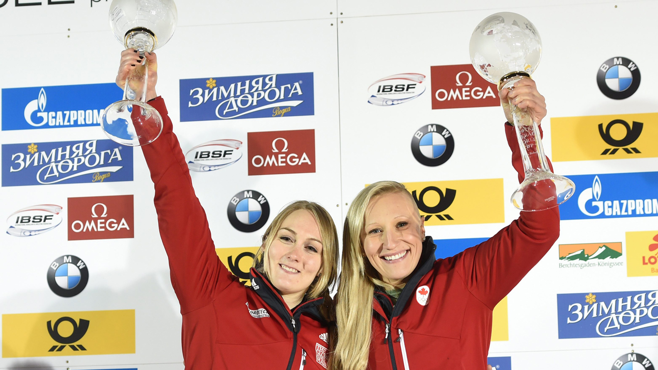 Kaillie Humphries and Melissa Lotholz holding up their trophies for the overall World Cup victory at Lake Koenigssee Germany February 26, 2016.