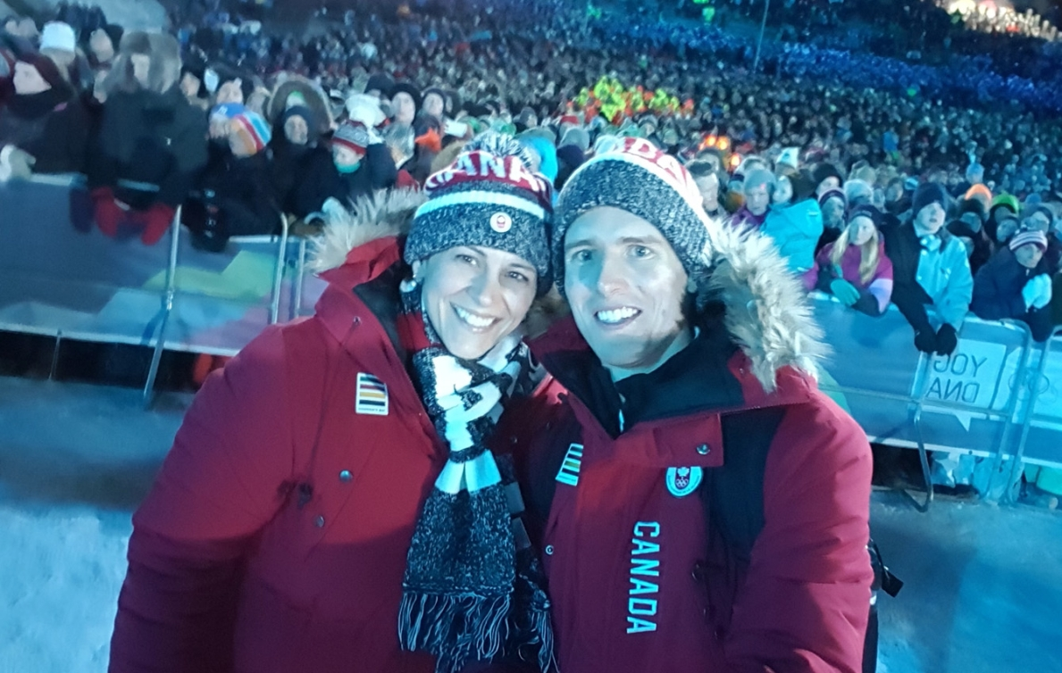 Two people dressed in Team Canada gear pose for a picture