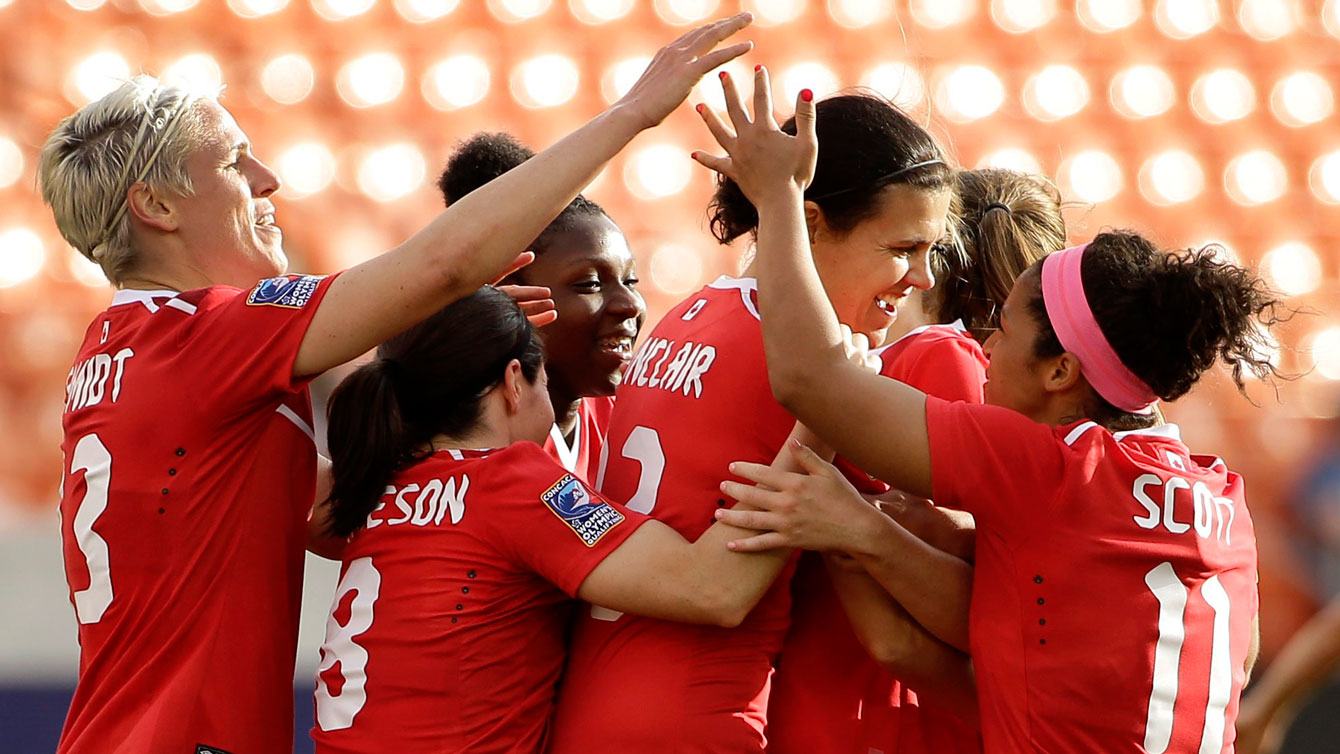Christine Sinclair (second from right) is congratulated by teammates after scoring her 159th career international goal on February 14, 2016.