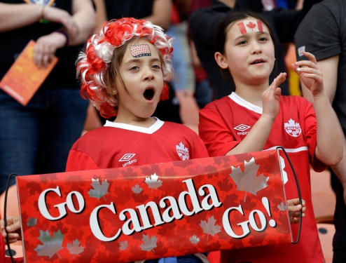 Two young Team Canada fans cheer for Canada's women's soccer team as they take the field for a CONCACAF Olympic qualifying tournament soccer match against. (AP Photo/David J. Phillip)
