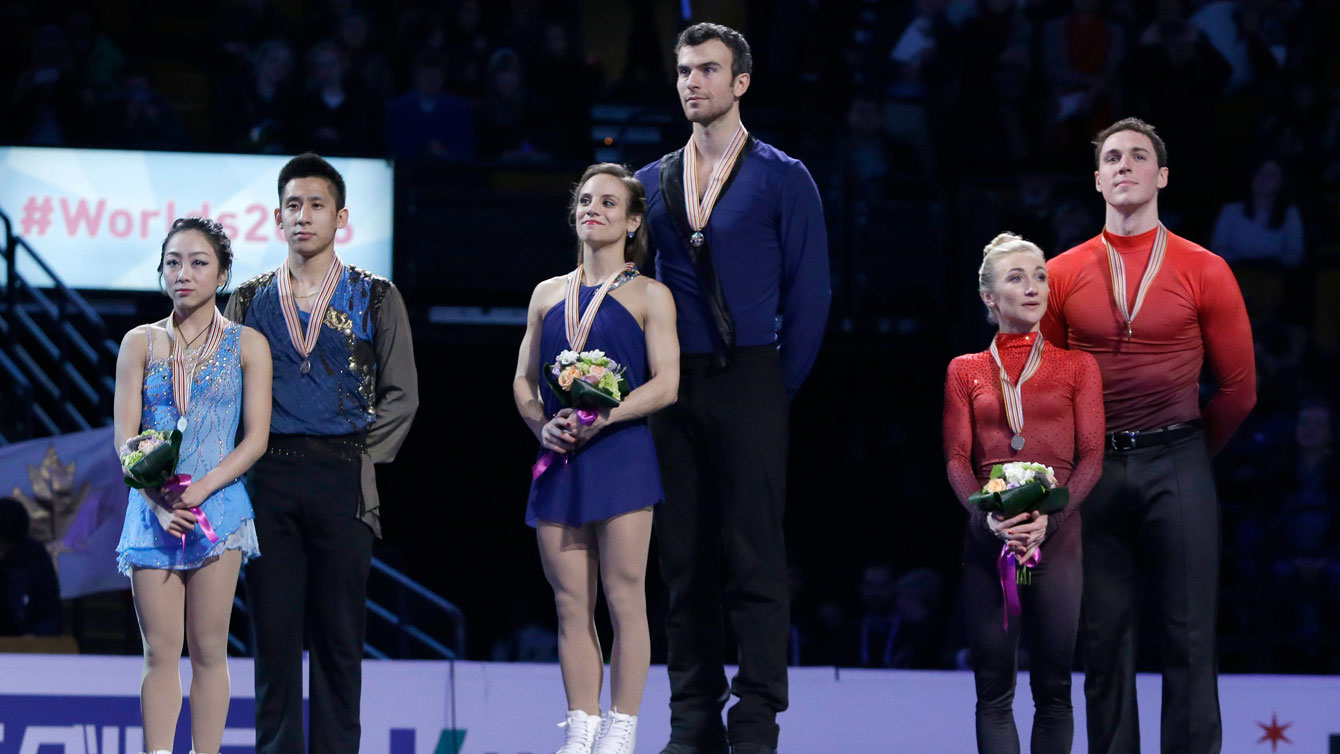 Meagan Duhamel and Eric Radford (centre) stand atop the pairs gold medal spot at the ISU Speed Skating World Championships podium ceremony on April 2, 2016.