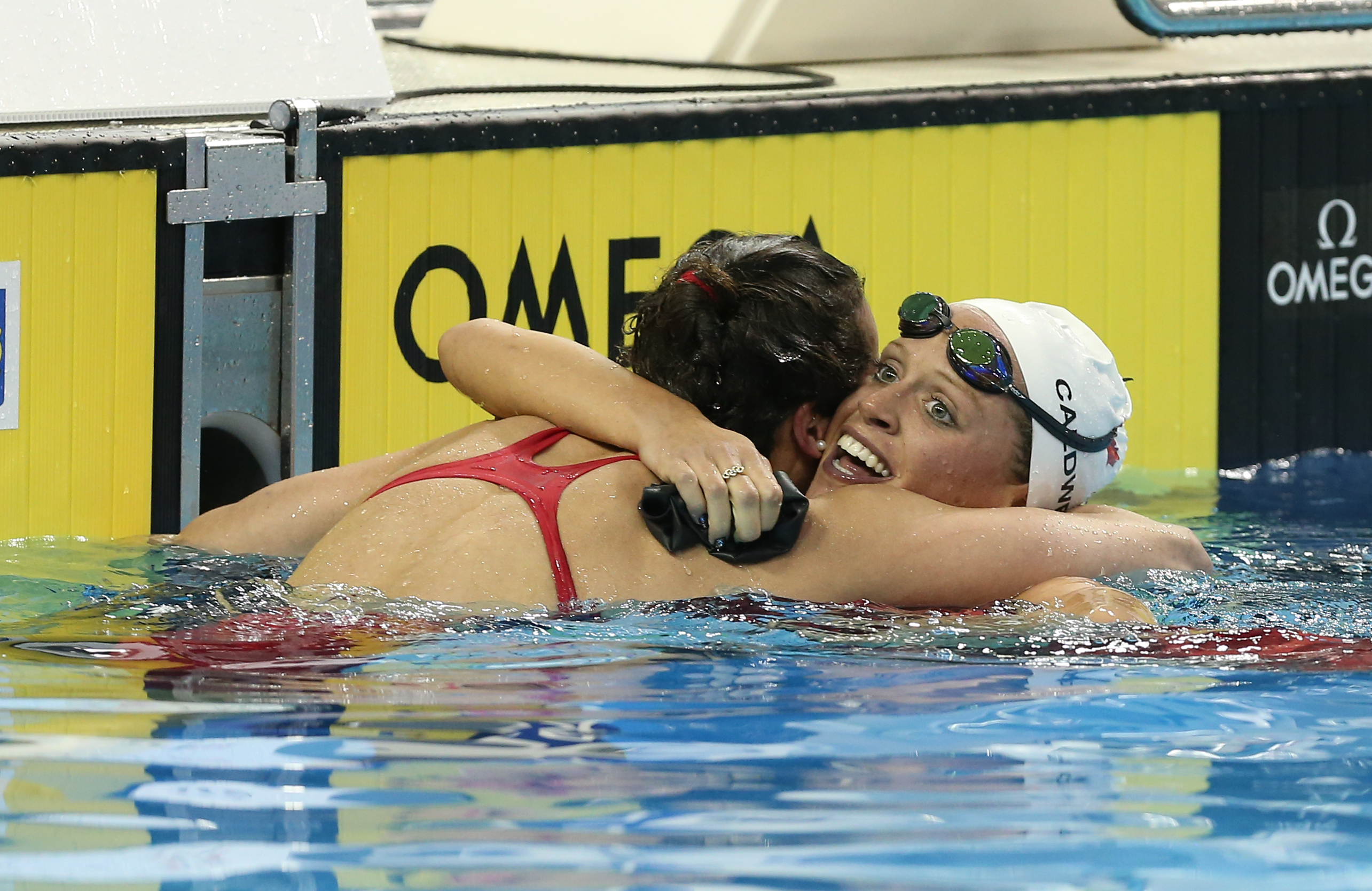 Hilary Caldwell (right) hugs a teammate after winning the 200m backstroke at Rio Trials on April 10, 2016 (Photo: Scott Grant via Swimming Canada).