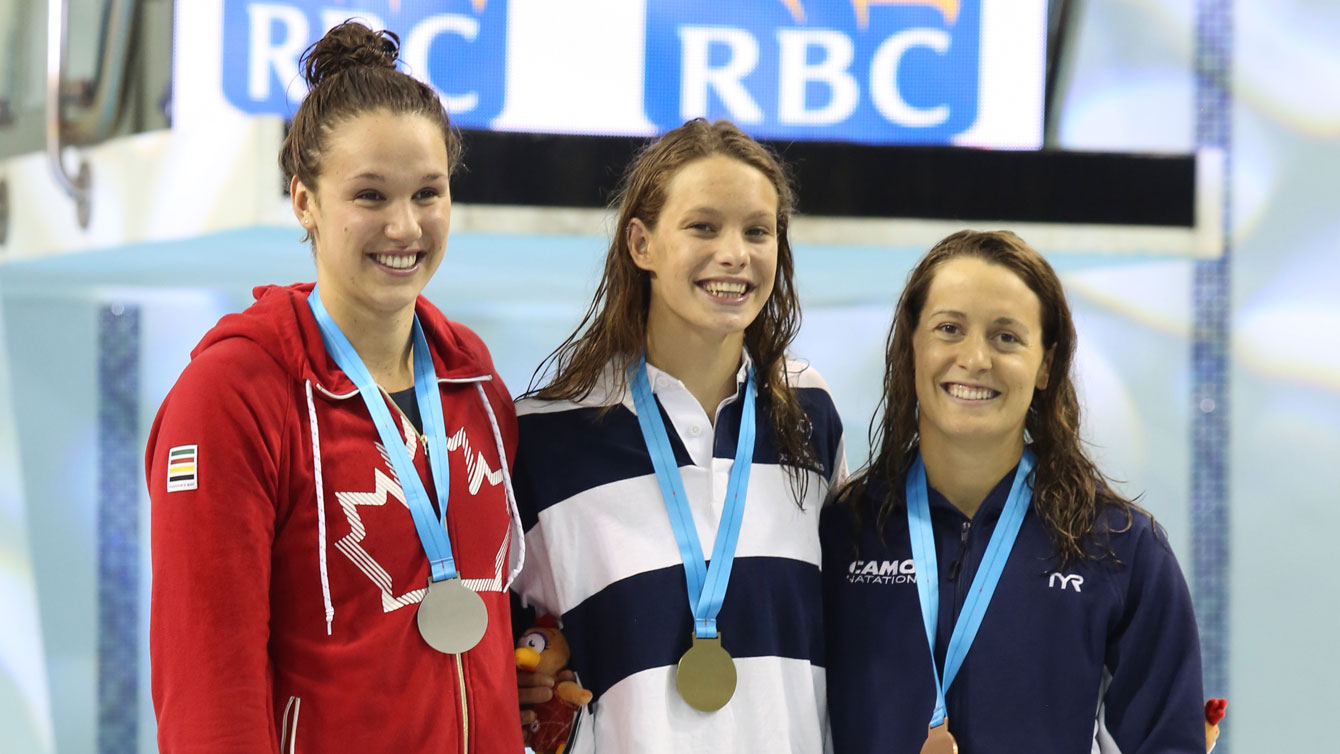 (L-R) Chantal Van Landeghem, Penny Oleksiak, Sandrine Mainville receiving their women's 100m freestyle medals from Rio Trials on April 9, 2016 (Scott Grant via Swimming Canada).