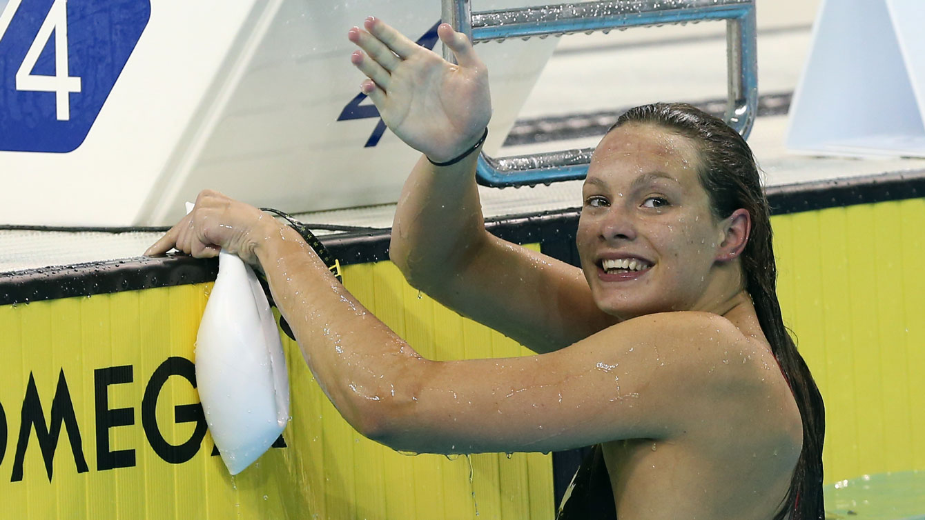Penny Oleksiak waves after a race