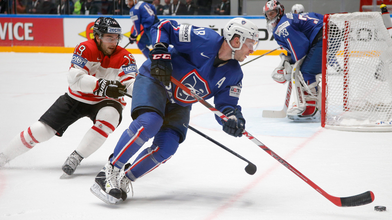 France's Yohann Auvitu, right, fights for the puck with Canada's Derick Brassard during the Hockey World Championships Group B match in St.Petersburg, Russia, Monday, May 16, 2016. (AP Photo/Dmitri Lovetsky)