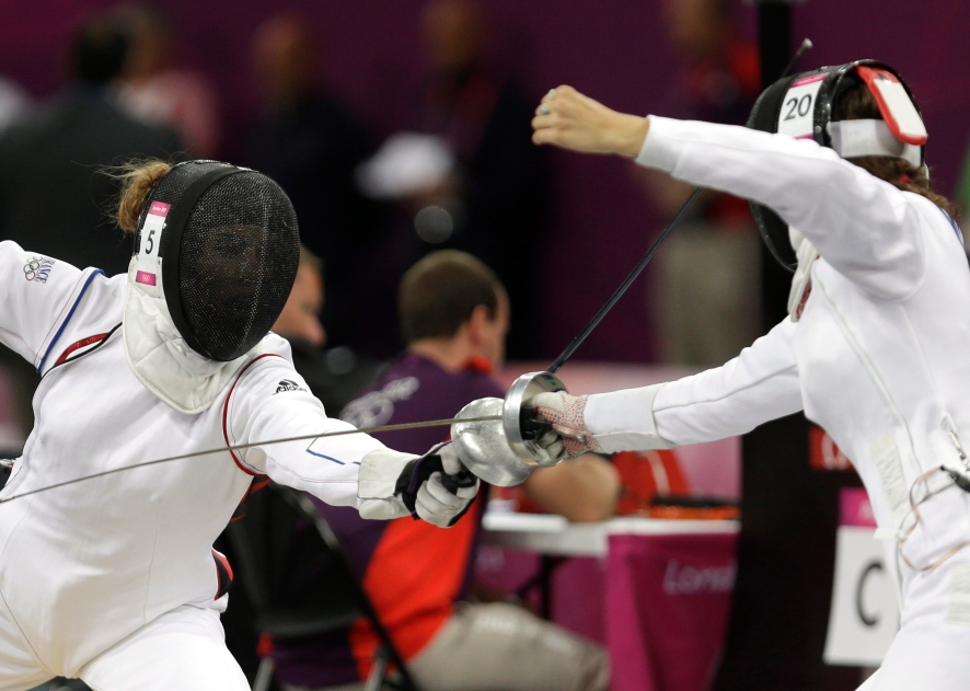 France's Elodie Clouvel, left, battles against Canada's Melanie McCann, right, during the fencing portion of the women's modern pentathlon competition at the 2012 Summer Olympics Sunday, Aug. 12, 2012, in London. (AP Photo/Hussein Malla)