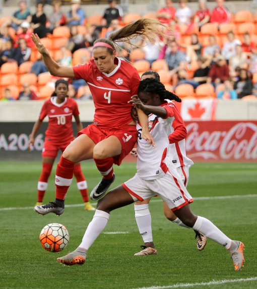 Canada's Shelina Zadorsky (4) jumps over the leg of Trinidad & Tobago's Khadidra Debesette (6) during the first half of a CONCACAF Olympic qualifying tournament soccer match Sunday, Feb. 14, 2016, in Houston. Canada won 6-0. (AP Photo/David J. Phillip)