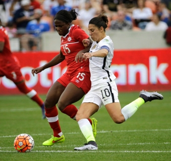 United States' Carli Lloyd (10) challenges Canada's Nichelle Prince (15) for the ball during the first half of the CONCACAF Olympic women's soccer qualifying championship final Sunday, Feb. 21, 2016, in Houston. (AP Photo/David J. Phillip)