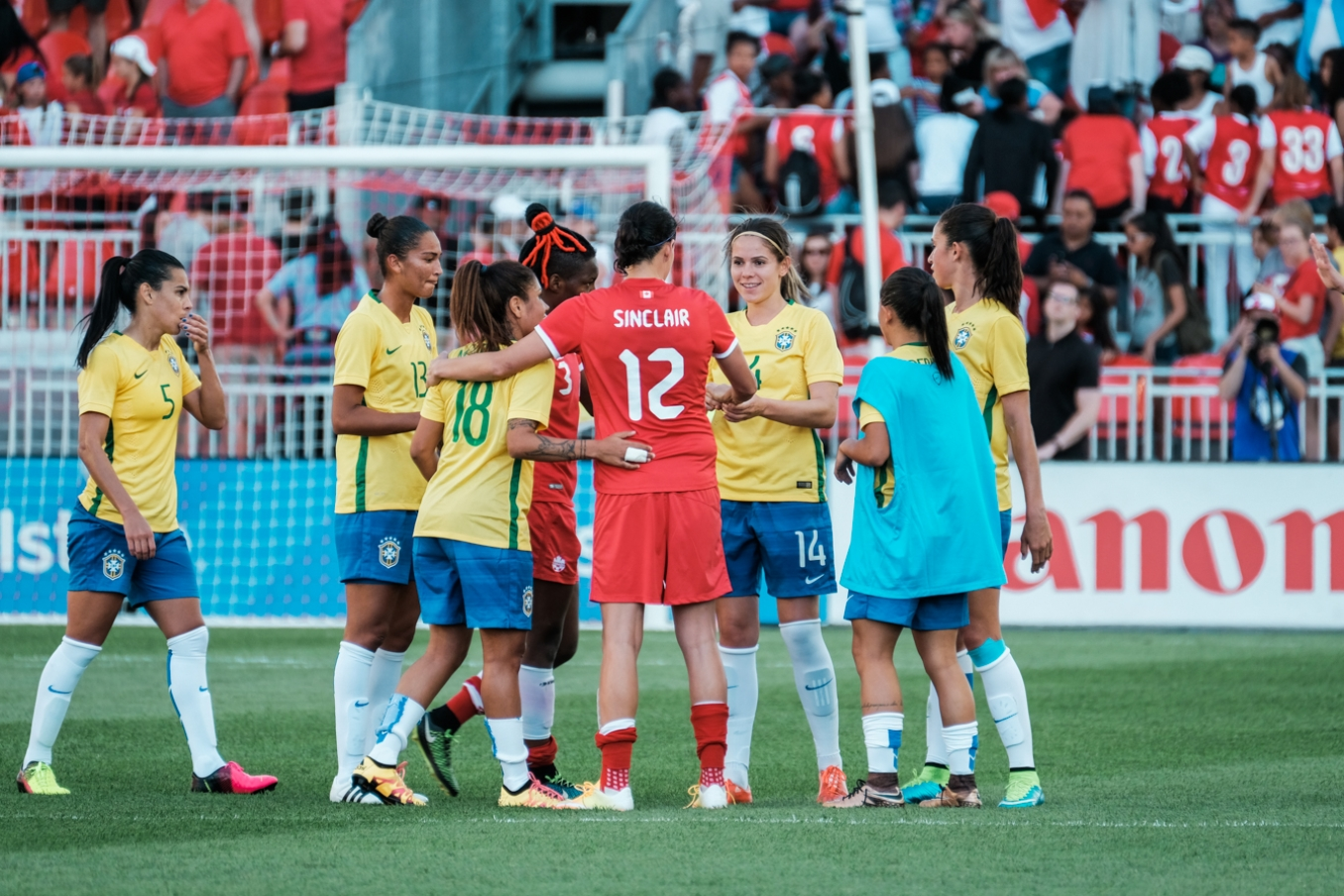 Canada and Brazil players exchange pleasantries at the end of the friendly